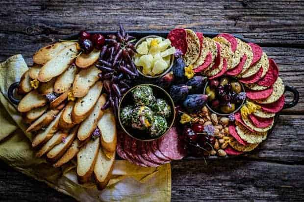 A giant oval shaped cheese platter. There are thinly sliced, toasted baguette pieces fanned out along one side of the dish. In the middle there are fresh red cherries, purple moon grapes, a gold metal bowl filled with edible flower and herb coated goat cheese, and a small ceramic dish of yellow dried pineapple. On the opposite side of the round dishes are fresh purple figs, more red cherries, and in-shell pistachios. There are red beet chips and white parmesan crisps alternating in color wrapped around the opposite end of the dish.