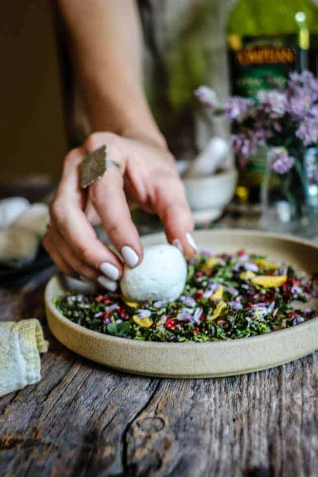 A woman's hand with white manicured nails wearing a large silver ring on her pointer finger, is holding a white ball of goat cheese over a plate filled with fresh minced herbs and edible flower blossoms. There is a vase of purple chive blossoms in teh background, a white mortar and pestle, and a bottle of olive oil.