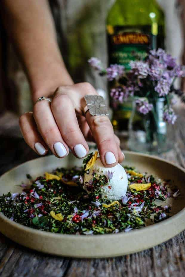 A woman's hand with white manicured nails wearing a large silver ring on her pointer finger, is holding a white ball of goat cheese over a plate filled with fresh minced herbs and edible flower blossoms. She has rolled half of the goat cheese ball in herbs and blossoms. There is a vase of purple chive blossoms in the background and a bottle of olive oil.