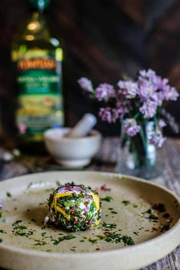 A cream colored dish sits on an old wooden table . On teh plate is a ball of goat cheese that has been rolled in freshly cut green herbs and edible flower blossoms. There is also a vase of chive blossoms, a white mortar and pestle, and bottle of olive oil on the table.