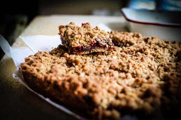Pieces of parchment on a table top with golden, gluten free oat bars on top. One bar is sitting on top of the rest. It has a golden brown crust, a layer of vibrant red cherry filling, then is topped with a golden crumble topping. There is a white and red baking pan in the back ground.