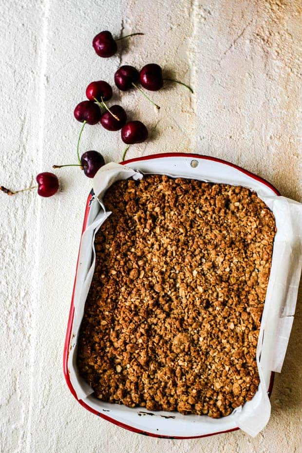 A white enamel pan with red trim is lined with parchment paper. The pan is filled with gluten free cherry oat bars that are golden in color. The pan is on top of a white surface with fresh cherries scattered across the top.
