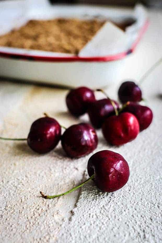 Fresh cherries scattered across a white surface. There is a white enamelware pan with red trim in the background that is filled with golden gluten free cherry oat bars.