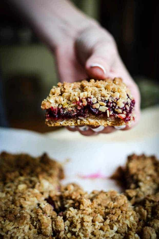 A woman's hand with white polished nails holding a cherry oat bar over a baking pan with more vbars in it. The bar has a golden crust, a vibrant red cherry filling, and a golden crumble oat crumble on top.