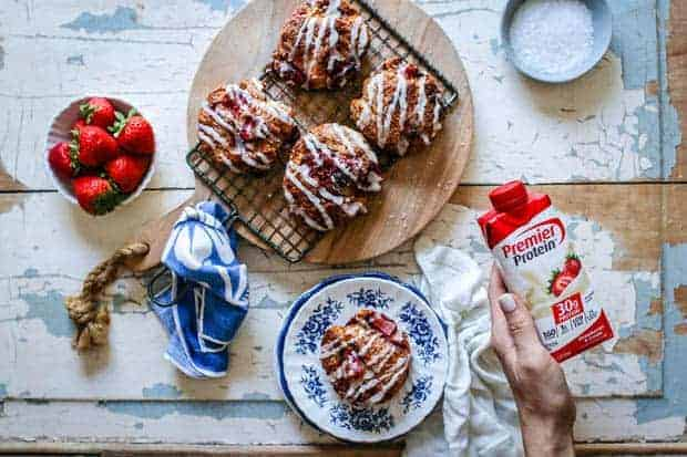 There is a round wooden cutting board on top of an old wooden table top that at one point was painted white and blue. The paint is cracking and peeling in places. On top of the cutting board there is a small metal cooling rack with a blue and white napkin tied around the handle. On top of the cooling rack there are 4 strawberry and cream scones that are golden brown with chunks of roasted strawberries and a white icing drizzle across the top. There is also a white bowl of strawberries, a blue bowl of sugar crystals, and a white plate with blue floral trim in the image on the table top. A woman's hand with white manicured nails is holding a red and white carton of Premier Protein Strawberry protein shake.