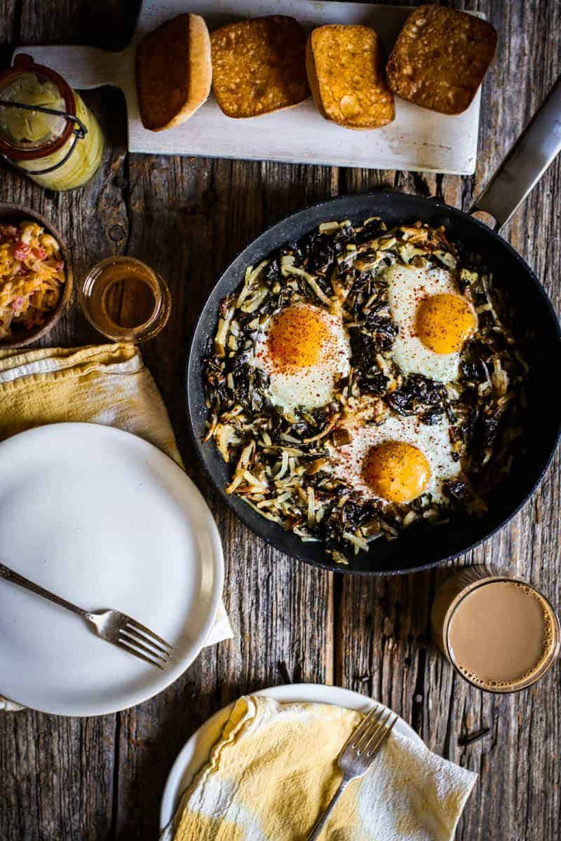 On top of a weathered wooden table is a skillet filled with a collard green and potato hash. The skillet has 3 perfectly cooked eggs with bright yellow yolks that are nestled in the greens and potatoes. There is a white wooden board on the table with 4 slices of toasted ciabatta bread. There is a small brown bowl with pigment cheese on the side of the skillet and a glass jar filled with broccoli stalk pickles. There are 2 white plates on the table with 2 yellow and white napkins. One place setting has a clear mug of coffee and there is a small clear glass filled with juice next to the other place setting.