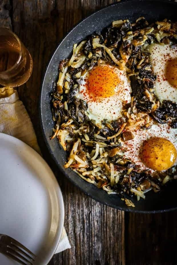 A skillet sits on top of weathered wooden table top. It is filled with a collard green and shredded potato hash and has 3 perfectly cooked eggs nestled inside the greens. There is also a white plate and a yellow napkin in the corner of teh image and a small glass of juice.