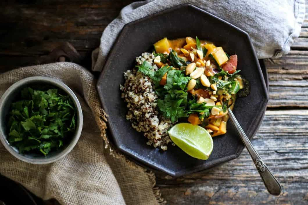 A black octagonal shaped bowl is filled with tri-colored quinoa, a spicy peanut soup that has chunks of butternut squash, sweet potato, and strips of collard greens. The soup is topped with chopped cilantro and coarsely chopped peanuts. There is a lime wedge on teh side of teh bowl and a spoon. Next to the soup is another small bowl of minced cilantro. Both of teh bowls are placed up in linen napkins that are on top of a weathered wooden table top.