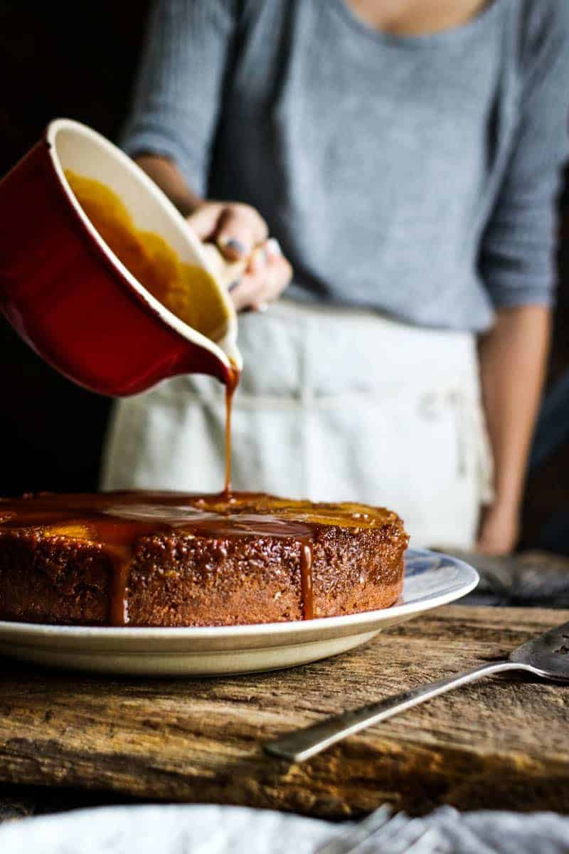 A golden colored round cake sits on a plate that is on top of a weathered wood board. There is a woman in a grey thermal shirt with a linen apron tied around her waist that is pouring hot caramel from a red saucepan over the top of the cake. The caramel is starting to drip down the sides of the cake onto the plate.