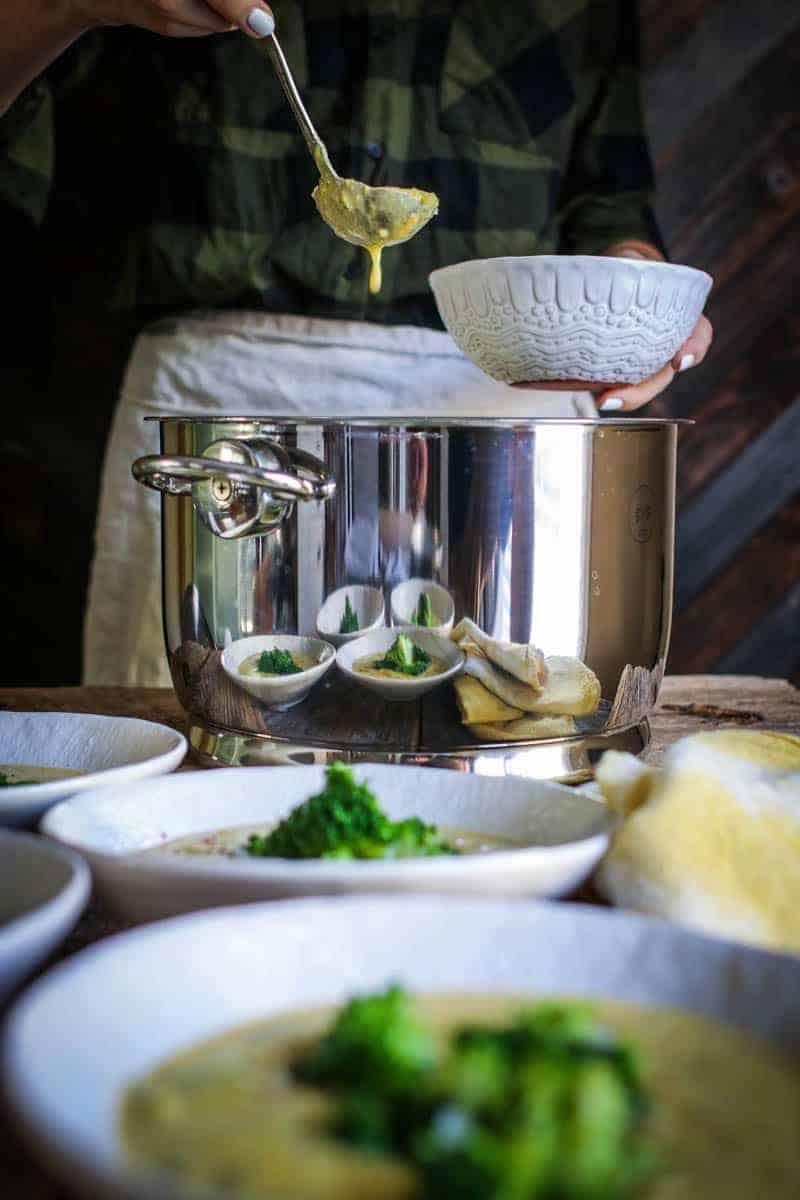 There are white bowls sitting on a table, they are filled with golden colored broccoli cheddar soup and topped with bright green broccoli florets. In the background there is a large silver soup pot behind the pot is a woman in a green and black flannel shirt and a tan linen apron tied around her waist. She is ladling soup from the silver pot into another white bowl with a silver ladle. There is a drop of soup dripping from the bottom of the ladle back into the pot.