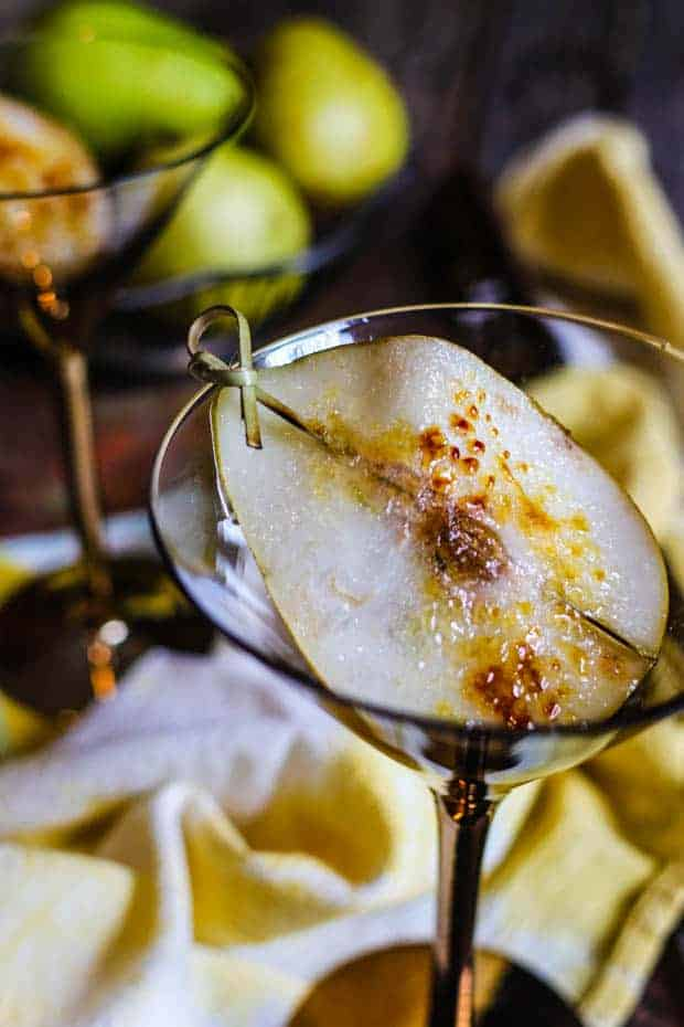 A close up image of a slice of pear that has been bruleed. The slice of pear has a bamboo cocktail pick through it and it is laud in a clear martini glass that has a gold stem. In teh background you can see a yellow and white cloth napkin, an empty martini glass, and a wire basket that has green pears in it.