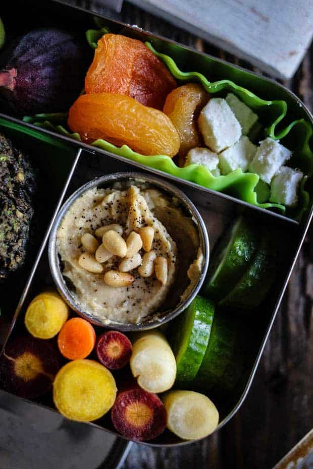 Close up of a stainless steel bento box. It is filled with Mediterranean inspired foods like hummus topped with pine nuts, rainbow carrots, sliced cucumbers, fresh figs, dried apricots, and feta.