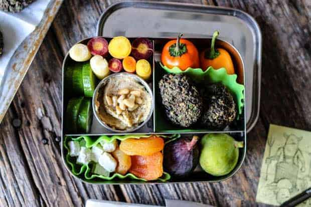 A stainless steel bento box packed with Mediterranean flavors of falafel, baby bell peppers, rainbow carrots, cucumbers, fresh figs, dried apricots.