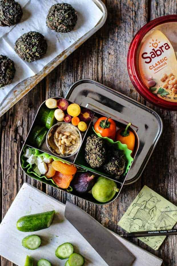 A stainless steel bento box is filled with falafel, baby bell peppers, rainbow carrots, cucumbers, apricots, fresh figs, feta, and hummus. The lunchbox is sitting on a weathered wooden table. There is a small white wooden cutting board in the bottom of the frame that has cucumbers sliced on it and a knife is laid on top. There is a drawing of a monster farmer wearing overalls on a yellow post it note. In the top corner of the image is a sheet pan lined with parchment paper. The parchment has pieces of falafel on top. There is also a container of Sabra Classic Hummus on the table.