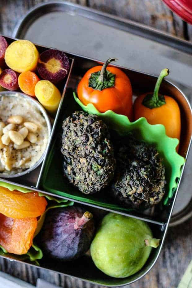 fresh figs, apricots, 2 falafel patties, 2 baby bell peppers, rainbow carrots, and a small dish of hummus with pine nuts are all packed in a stainless steel bento box