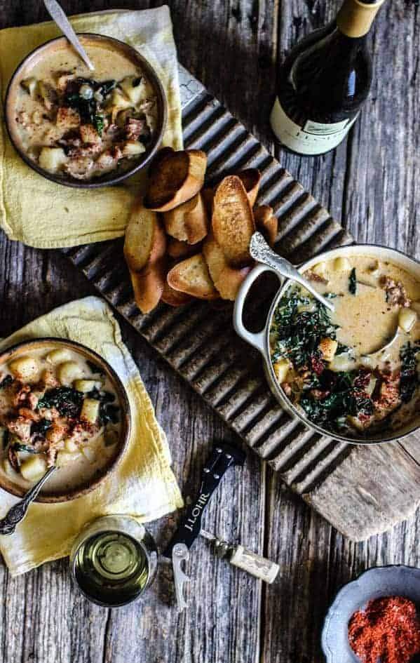 A rustic tablescape made up of a weathered wooden table top set with 2 light brown handmade bowls and a cream Le Cruset Dutch oven, filled with Zuppa Toscana Soup. The soup is cream based and has potatoes, sausage, and kale.In between the bowls is a pile of sliced, toasted baguette pieces. There are yellow linen napkins underneath the bowls. Silver spoons in the small bowls and a silver ladle in the Dutch oven. A bottle of chardonnay and a wine glass sit on the table as well as a small brown bowl of red pepper flakes in the corner. In teh middle of the table is a black handle wine key.
