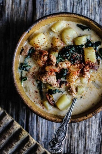 A light brown handmade soup bowl sits on a weathered wooden table top The bowl is filled with Zuppa Toscana soup, which is a creamy soup made from potatoes, sausage, and kale. There is an antique silver spoon in the bowl. The corner of a rustic chopping board is in the bottom left corner of the image.