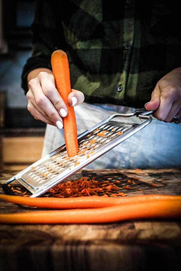 A woman is grating a carrot on a metal grater that is sitting on top of a wooden chopping block. There are 2 orange carrots laying on teh chopping block as well as a pile of shredded carrots. The woman is wearing a green and black flannel shirt and has a tan linen apron tied around her waist.