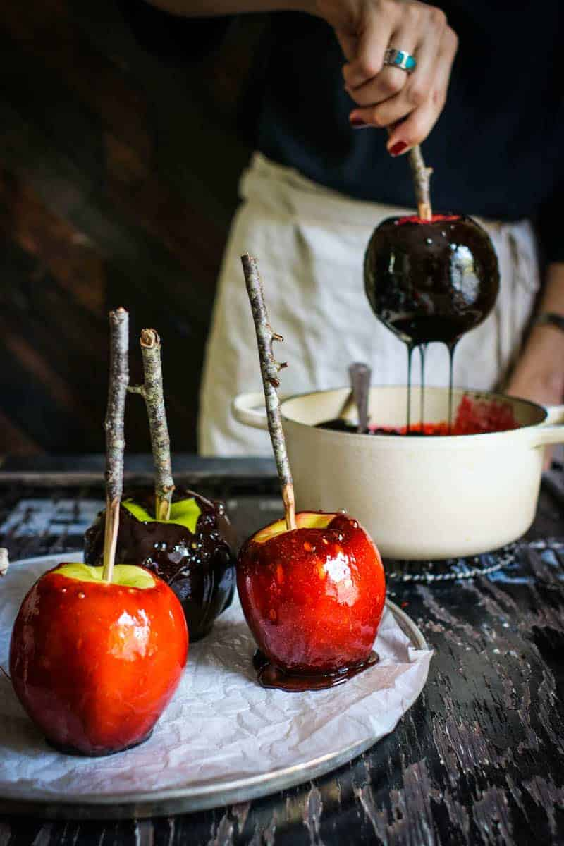 There is a woman in a black shirt and linen apron in the background dipping a red apple into a black candy syrup. There are 2 red candy apples and 1 black candy apple that are sitting on a metal tray at the front of the table the woman is standing at.