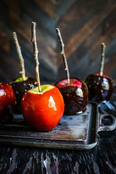 5 candy apples are sitting on top of a metal tray on a black table top. 2 of teh candy apples are red and 3 are black. The candy apple's sticks are made from real tree branches.