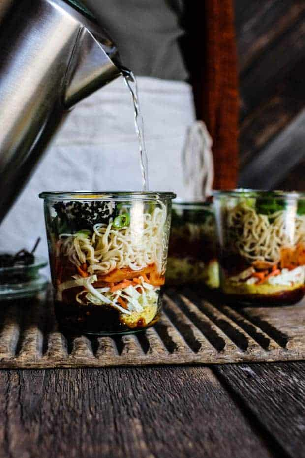 A woman in a green thermal shirt with a orange sweater is pouring hot water from a kettle into a jar that is layered with gluten free cup of noodles with kimchi. There are 2 other jars of noodle ingredients sitting on the wooden table next to the woman.