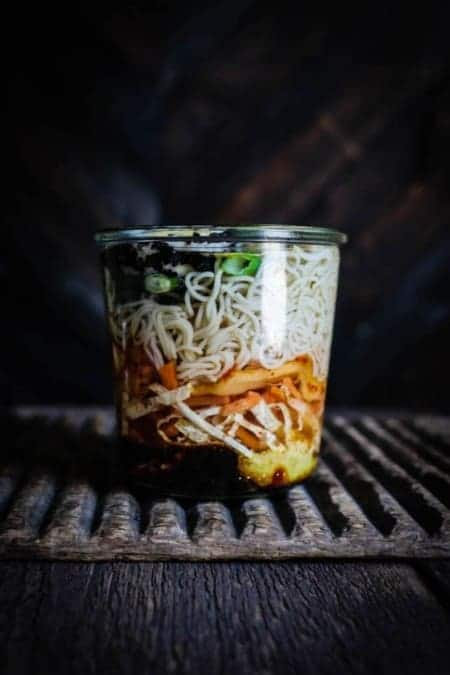 A glass week jar filled with the ingredients for messing gluten free cup of noodles with kimchi sits on a wooden table in front of a dark wood wall.
