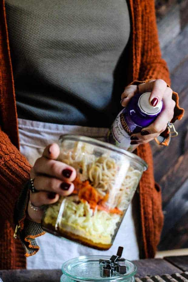A woman in a green thermal short and orange sweater with a linen apron is holding a jar of ramen noodles and vegetables in one hand and spraying a can of grapeseed oil into the jar with the other hand.