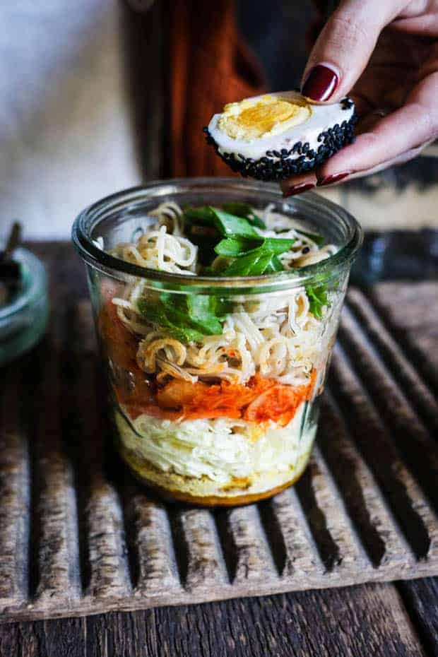 A glass jar layered with kimchi cup o noodles ingredients is sitting on wooden table. A woman with red manicured fingernails is putting half of a hard boiled egg that has been rolled in black sesame seeds.