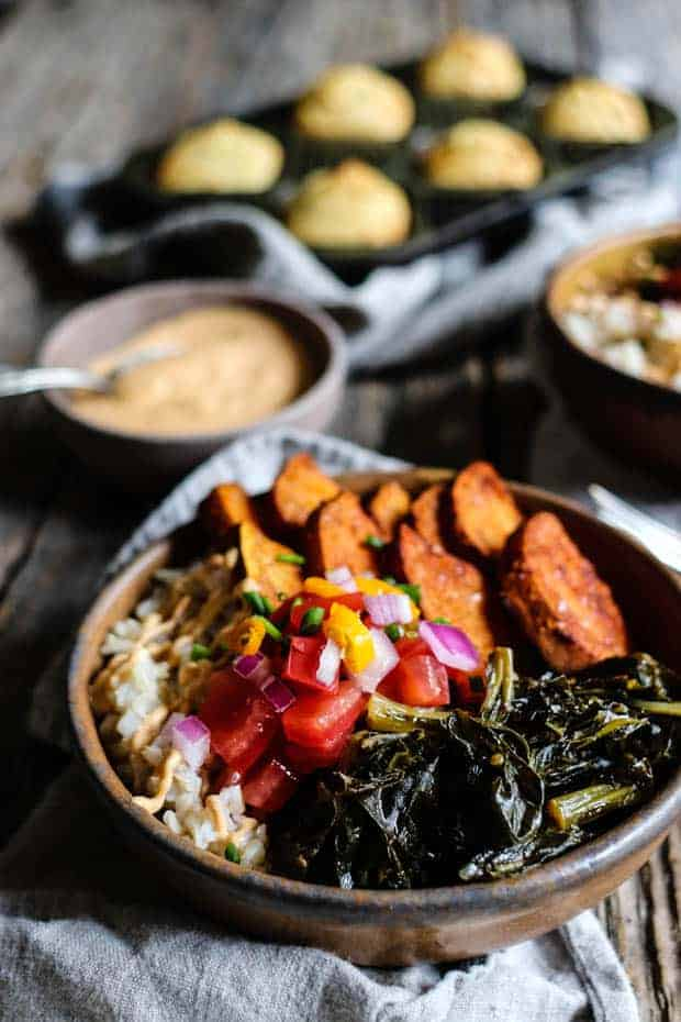 A bowl filled with brown rice, roasted sweet potatoes, collard greens, and pico de gallo sits on top of a line napkin on a table top. There is a small bowl of chipotle cashew cream in the background as well as pan of cornbread muffins.