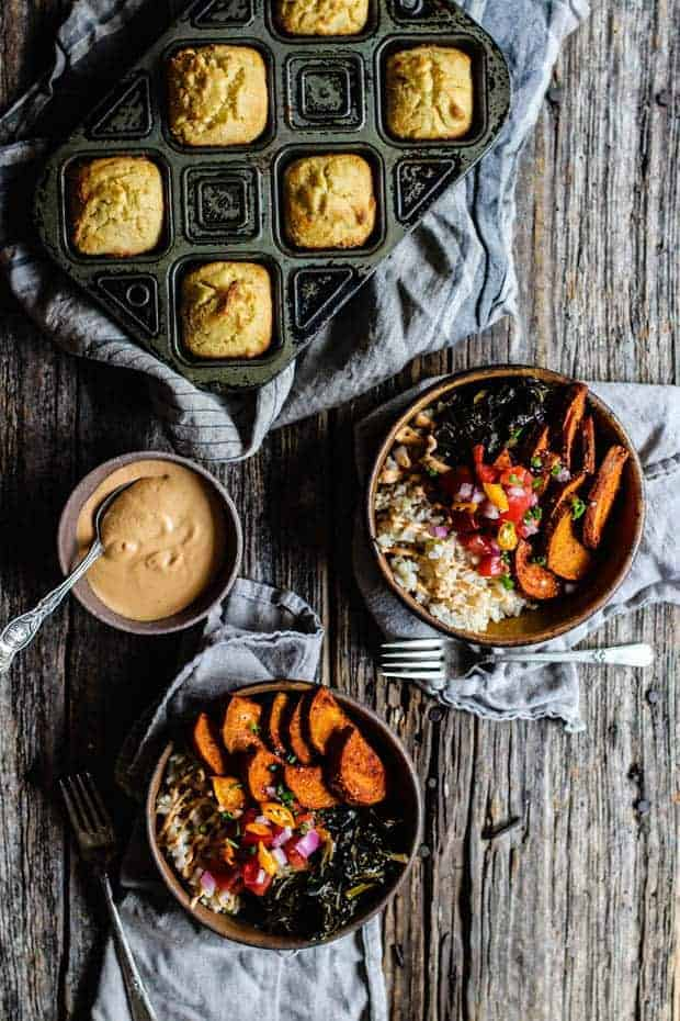 2 bowls filled with brown rice, collard greens, roasted sweet potatoes, and pic de gallo are on a wooden table top. There is a small bowl of chipotle cashew cream and a pan of cornbread muffins on testable as well as linen napkins and a few forks.