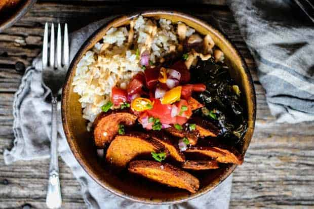 A handmade bowl filled with brown rice, sweet potatoes, collard greens, and pico de gallo is sitting on a wood table top with a fork and linen napkin next to it.