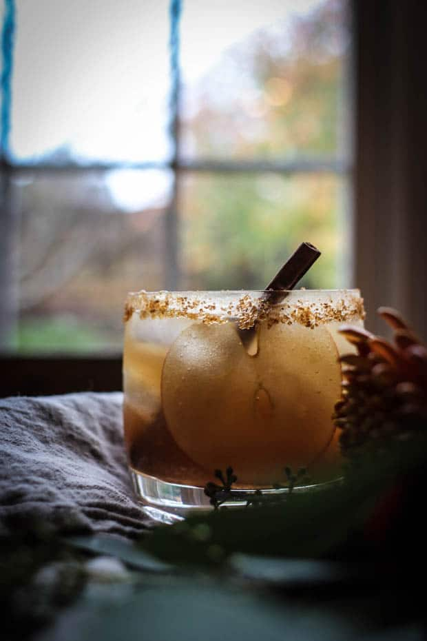 A festive cocktail with a thin slice of apple, a cinnamon stick, and a brown sugar cinnamon rim sits on a table with greenery and linens in front of a window that looks out upon trees that are full of autumn colored leaves.