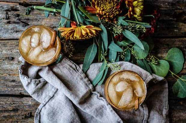 2 Spiked Apple Cider Cocktails with ice and a linen napkin are set upon a worn wooden table. There are also yellow and orange flowers laid on the table.
