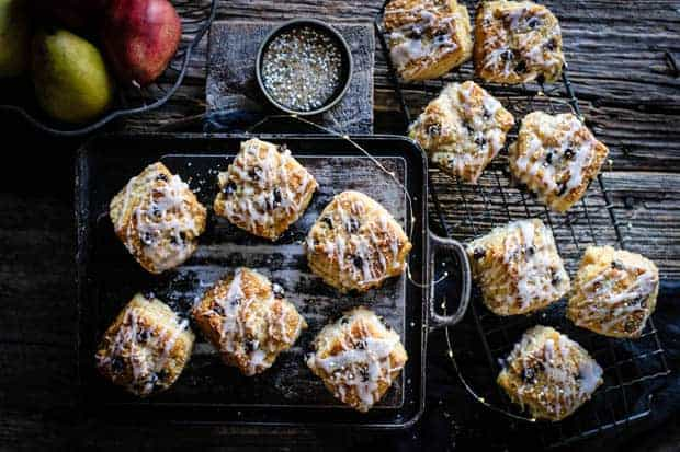 Dark chocolate pear scones that are drizzled with pear icing and sparkling sugar are sitting on top of a metal baking pan and some on a wire cooling rack. There are red and green pears in a bowl off to the side and a small black shallow dish filled with sparkling sugar on the table.