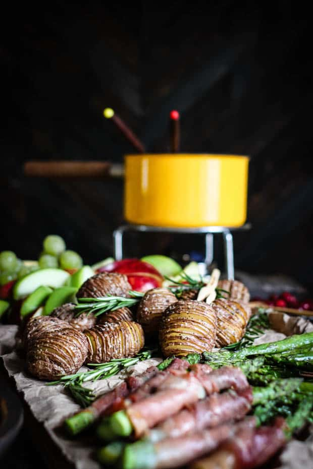 A vintage yellow fondue pot is in the background of the image on a wood board covered in brown parchment paper in front of the fondue pot is roasted prosciutto wrapped asparagus spears, hasselback potatoes, and sliced red and green apples.