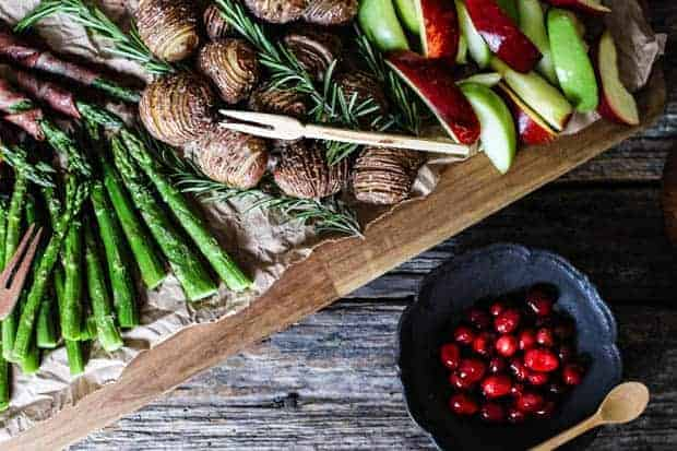There is a large wooden food board on a wooden table top. The board is piled high with roasted asparagus spears, prosciutto wrapped asparagus spears, hasselback potatoes, and red and green apple slices. There is a bowl of pickled cranberries next to the board.