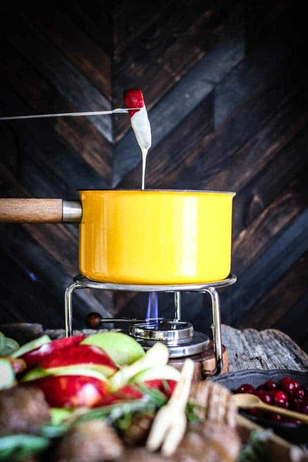 A slice of red apple is on a fondue fork. The fondue fork has dunked down in a yellow fondue pot and teh apple slice is half dipped in cheese fondue. In front of the fondue pot there is a pile of red and green apple slices, hasselback potatoes, and a bowl of pickled cranberries.