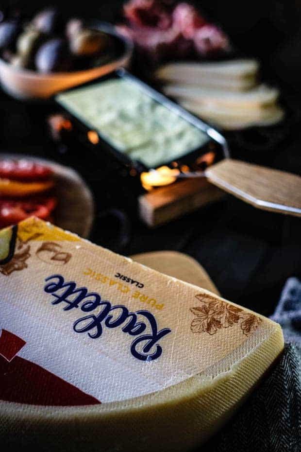 A wheel of raclette cheese and a small personal raclette burner are sitting on a table top with other items used for raclette - sliced cheese, meats, boiled potatoes, and sliced tomatoes