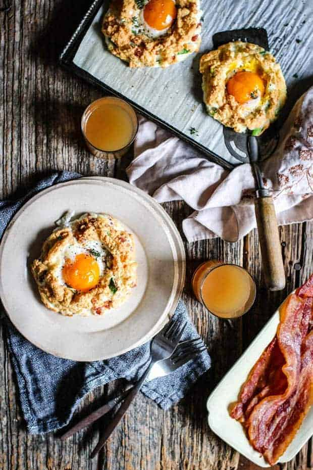 A baking sheet lined with parchment has 2 cloud eggs on it, one has a spatula underneath it. There are 2 glasses of juice on the table, a cream colored plate with bacon on it and a white plate sitting on top of a cloth napkin has a cloud egg on it as well.