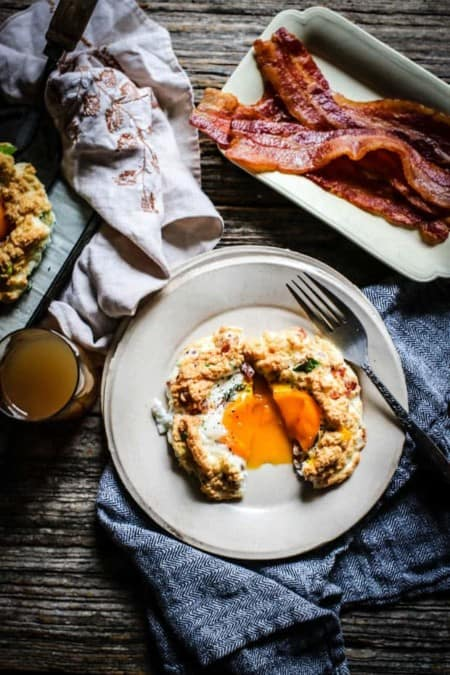 A cloud egg is cut in half on a cream colored plate, there is egg yolk spilling out onto teh plate. The plate is on a black and white napkin on top if a weathered wooden table. there is a small plate of bacon and a glass of juice on the table too.
