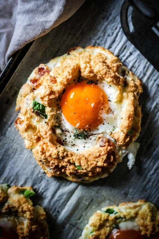 Pillowy, fluffy egg whites folded with crispy bacon pieces, Parmesan, and scallions are mounded on a baking sheet, topped with an egg yolk and baked until perfectly golden. The baked cloud eggs are on a baking sheet lined with parchment paper. There is also a spatula and a cloth napkin.