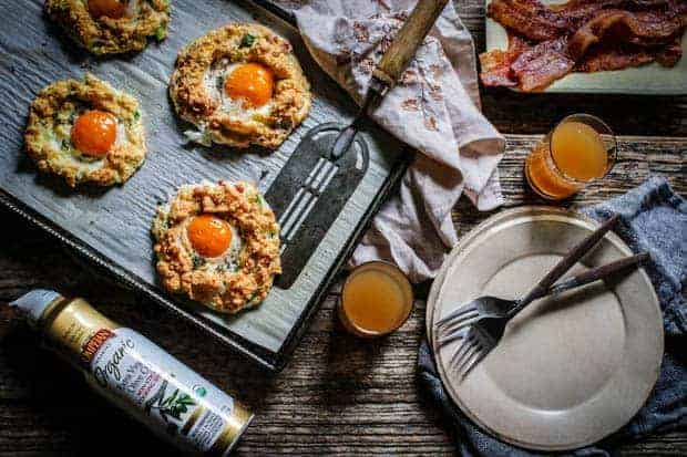 A parchment paper lined sheet pan has 4 cloud eggs on it and a vintage spatula. There are plates on teh table and forks, cloth napkins and 2 small clear glass filled with juice. there is a bottle of Pompeian olive oil spray on the table and a plate of bacon.