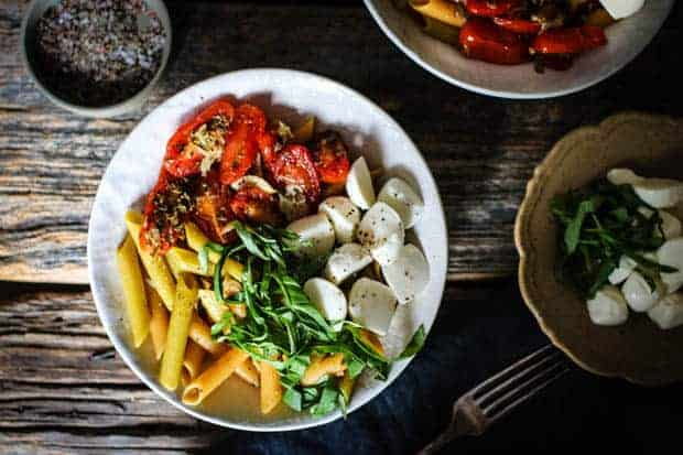 A white bowl is filled with pasta, oven roasted tomatoes, basil ribbons, and mozzarella balls. The bowl is on a weathered wooden table top along with a small bowl of mozzarella;la and basil and a shallow dish of ground pepper.