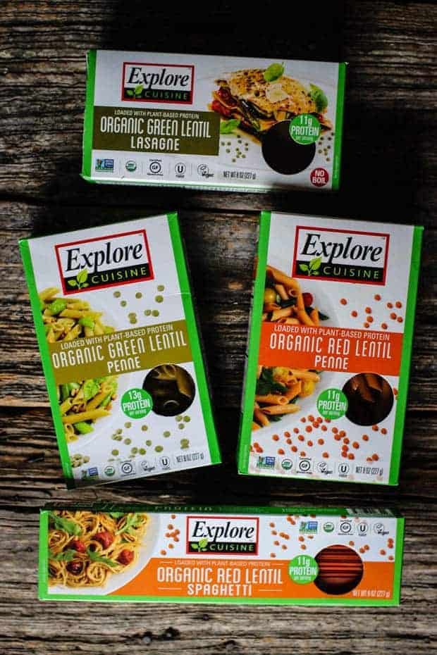 4 boxes of Explore Cuisine Organic Pasta made with red and green lentils are sitting on a wooden table top.