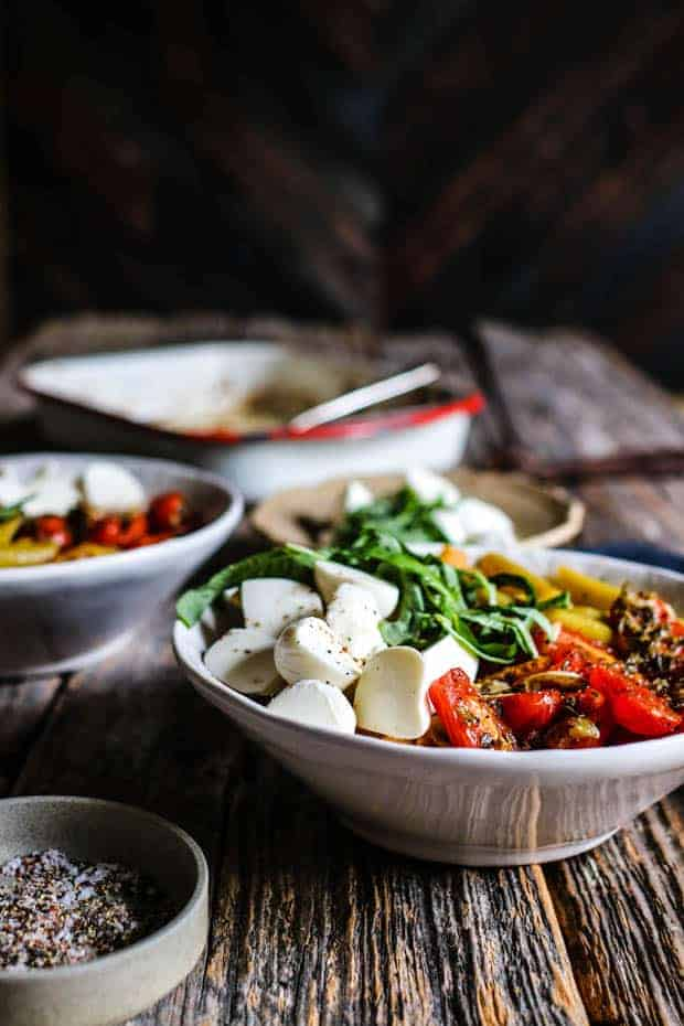 Close up of a bowl of roasted caprese pasta salad with pasta, roasted tomatoes, mozzarella balls, and basil. There is small bowl of pepper and a baking dish with extra roasted tomatoes on the table top.