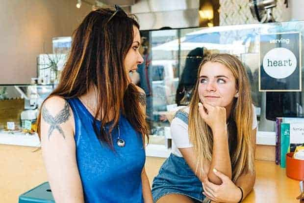 A woman in a blue sleeveless shirt and a girl in a blue jean overall dress and white t-shirt are sitting in a cafe.