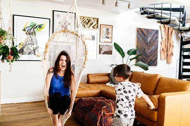 A woman is in a macrame swing, a little boy in a white and black t-shirt is pushing her. She is laughing. They are in a room with a black spiral staircase in the back and lots of colorful artwork on the walls.