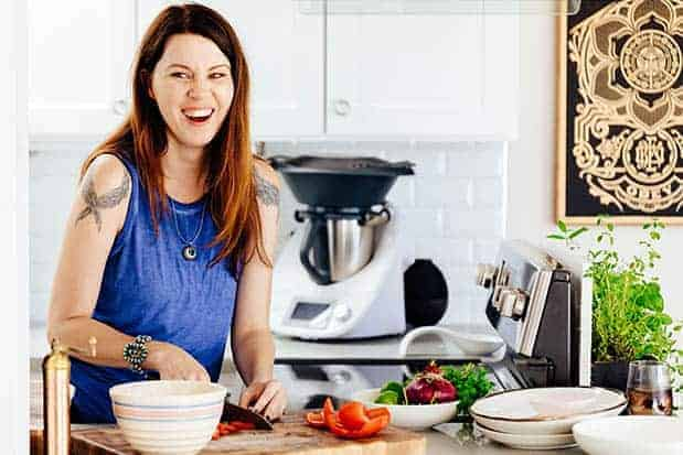 A woman in a blue shirt with long brown hair is in a white kitchen chopping vegetables on a cutting board. There are serving dishes on the counter in front of her.