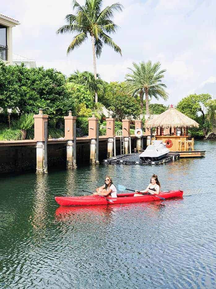 2 girls in a red canoe on the water in Boca Raton Florida. There is a floating tiki hut and palm trees behind them.