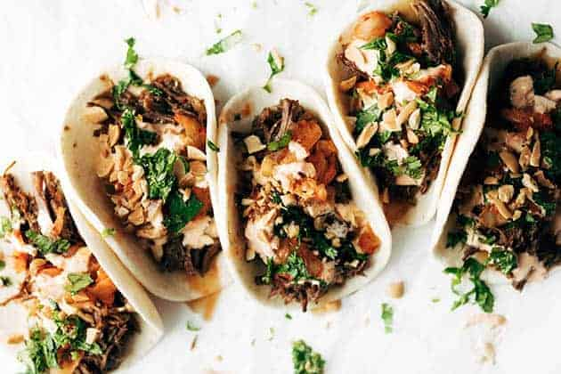 5 flour tortillas filled with taco fixings; Korean beef, kimchi, chopped peanuts, and cilantro